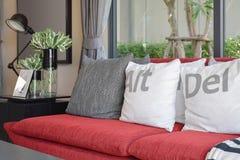 Σύγχρονο σχέδιο καθιστικών με τα μαξιλάρια στον κόκκινο καναπέ Στοκ Εικόνα