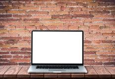 Σύγχρονο lap-top με την κενή άσπρη οθόνη στον ξύλινο πίνακα ενάντια στο θολωμένο παλαιό τουβλότοιχο στοκ φωτογραφίες με δικαίωμα ελεύθερης χρήσης