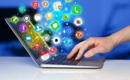 Σύγχρονο lap-top συμπίεσης χεριών με τα κινητά app εικονίδια και τα σύμβολα Στοκ φωτογραφία με δικαίωμα ελεύθερης χρήσης