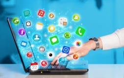 Σύγχρονο lap-top συμπίεσης χεριών με τα κινητά app εικονίδια και τα σύμβολα Στοκ Φωτογραφίες