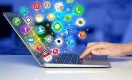 Σύγχρονο lap-top συμπίεσης χεριών με τα κινητά app εικονίδια και τα σύμβολα Στοκ Εικόνα