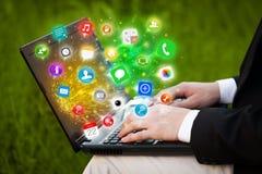 Σύγχρονο lap-top συμπίεσης χεριών με τα κινητά app εικονίδια και τα σύμβολα Στοκ Φωτογραφία