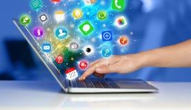 Σύγχρονο lap-top συμπίεσης χεριών με τα κινητά app εικονίδια και τα σύμβολα Στοκ Εικόνες