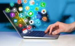 Σύγχρονο lap-top συμπίεσης χεριών με τα κινητά app εικονίδια και τα σύμβολα Στοκ εικόνες με δικαίωμα ελεύθερης χρήσης