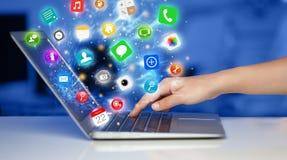 Σύγχρονο lap-top συμπίεσης χεριών με τα κινητά app εικονίδια και τα σύμβολα Στοκ φωτογραφίες με δικαίωμα ελεύθερης χρήσης