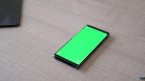 Σύγχρονο smartphone με την πράσινη χλεύη χρώματος οθόνης που βρίσκεται επάνω στο γραφείο απόθεμα βίντεο