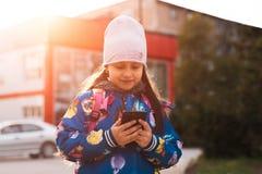 Σύγχρονο smartphone χρήσης κοριτσιών παιδιών σε υπαίθριο με το φως του ήλιου στοκ φωτογραφίες
