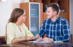 Σύζυγοι με τα έγγραφα για την τράπεζα στο σπίτι Στοκ Εικόνες