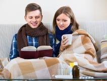 Σύζυγοι που έχουν το σωλήνα μαζί, καθμένος με το βιβλίο και το τσάι Στοκ Φωτογραφία