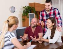 Σύζυγοι που κάθονται με τα έγγραφα και που ρωτούν τους φίλους για τις συμβουλές Στοκ Φωτογραφίες