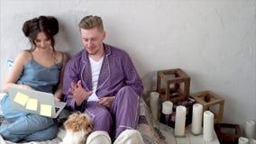 Σύζυγος και σύζυγος με να κάνει σημειωματάριων ψωνίζοντας on-line και παίζοντας με το σκυλί στο κρεβάτι απόθεμα βίντεο