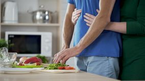 Σύζυγος που αγκαλιάζει ήπια το σύζυγό της που μαγειρεύοντας φυτική σαλάτα για το οικογενειακό μεσημεριανό γεύμα απόθεμα βίντεο