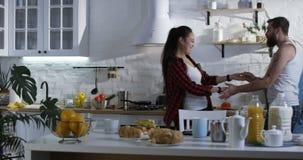 Σύζυγος που ενώνει τη σύζυγό του στην κουζίνα για το πρόγευμα φιλμ μικρού μήκους