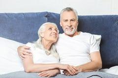 Σύζυγος που εξετάζει το σύζυγό της που προσέχει τη TV στοκ φωτογραφίες