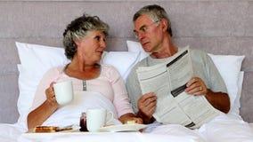 Σύζυγος που διαβάζει την εφημερίδα στη σύζυγό του κατά τη διάρκεια του προγεύματος απόθεμα βίντεο