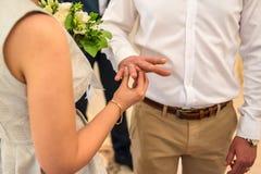 Σύζυγος που φορά ένα γαμήλιο δαχτυλίδι στο δάχτυλο στο σύζυγό της στοκ φωτογραφία