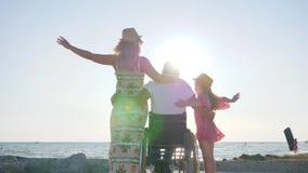 Σύζυγος στη σύζυγο αγκαλιάσματος καρεκλών ροδών και μικρό κορίτσι στο backlight απόθεμα βίντεο
