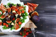 Σύκα, αραιά τεμαχισμένο ιταλικό ζαμπόν και τρυφερή σαλάτα τυριών στο άσπρο πιάτο στον ξύλινο πίνακα με τα συστατικά στο υπόβαθρο, στοκ εικόνες