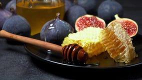 Σύκα με το μέλι επάνω στο πιάτο στο σκοτεινό συγκεκριμένο υπόβαθρο απόθεμα βίντεο