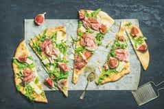 Σύκο, prosciutto, arugula και λογική πίτσα flatbread στο σκοτεινό υπόβαθρο Στοκ Εικόνες