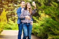 Σύλληψη των φωτεινών στιγμών Χαρούμενο νέο αγαπώντας ζεύγος που κάνει selfie στη κάμερα στοκ φωτογραφία