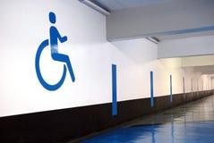 Σύμβολο αναπηρίας που χρωματίζεται σε έναν υπόγειο τοίχο χώρων στάθμευσης ελεύθερη απεικόνιση δικαιώματος