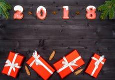 Σύμβολο σημαδιών καλής χρονιάς 2018 από τα κόκκινα και άσπρα μπισκότα μελοψωμάτων στο σκοτεινό ξύλινο υπόβαθρο με τα κόκκινα κιβώ Στοκ εικόνα με δικαίωμα ελεύθερης χρήσης