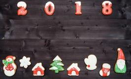 Σύμβολο σημαδιών καλής χρονιάς 2018 από τα κόκκινα και άσπρα μπισκότα μελοψωμάτων στο σκοτεινό ξύλινο υπόβαθρο, διάστημα αντιγράφ Στοκ Εικόνα