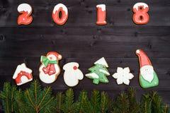 Σύμβολο σημαδιών καλής χρονιάς 2018 από τα κόκκινα και άσπρα μπισκότα μελοψωμάτων στο σκοτεινό ξύλινο υπόβαθρο, διάστημα αντιγράφ Στοκ Φωτογραφία