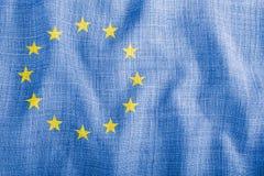 Σύμβολο της ΕΕ σε ένα υπόβαθρο του μπλε κυματιστού υφάσματος στοκ φωτογραφία με δικαίωμα ελεύθερης χρήσης