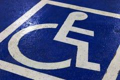Σύμβολο χώρων στάθμευσης για τα άτομα με ειδικές ανάγκες στην εκλεκτική εστίαση υπαίθριων σταθμών αυτοκινήτων στοκ εικόνα