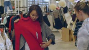 Σύμβουλος και αγοραστής στις γυναίκες που ντύνουν το κατάστημα απόθεμα βίντεο