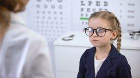 Σύμβουλος που βοηθά το παιδί για να επιλέξει eyeglasses μόδας, υπηρεσία στο οπτικό κατάστημα απόθεμα βίντεο