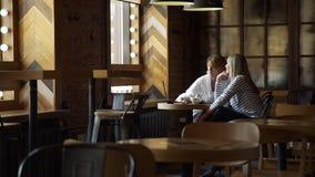 Σύμβουλος που παρουσιάζει προσφορά στον πελάτη στο lap-top στον καφέ απόθεμα βίντεο