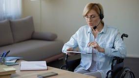 Σύμβουλος ταξιδιωτικού γραφείου στην αναπηρική καρέκλα που ψάχνει τον κατάλληλο γύρο στην ταμπλέτα απόθεμα βίντεο