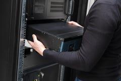 Σύμβουλος εγκαθιστά το δρομολογητή δικτύων στο datacenter στοκ εικόνα με δικαίωμα ελεύθερης χρήσης