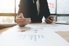Σύμβουλος επένδυσης επιχειρησιακών ατόμων που αναλύει το ετήσιο fina επιχείρησης Στοκ Εικόνες