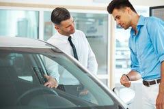 Σύμβουλος πωλήσεων αυτοκινήτων που παρουσιάζει νέο αυτοκίνητο σε έναν πιθανό αγοραστή στο S Στοκ Εικόνες