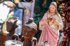 Σύμβολα θρησκείας πολυθεϊσμού, Χριστός και ξύλινα αφρικανικά αγάλματα στην πώληση γκαράζ στοκ εικόνα με δικαίωμα ελεύθερης χρήσης