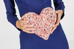 Σύμβολο ημέρας βαλεντίνων καρδιών εκμετάλλευσης κοριτσιών Καρδιά η αγάπη ανασκόπησης κόκκινη αυξήθηκε λευκό συμβόλων ISO Στοκ Φωτογραφίες