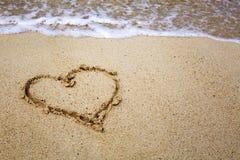 Σύμβολο καρδιών στο κύμα άμμου και θάλασσας Στοκ Φωτογραφίες