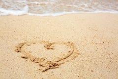 Σύμβολο καρδιών στο κύμα άμμου και θάλασσας Στοκ Εικόνες