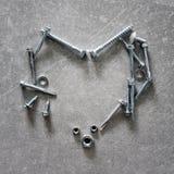 Σύμβολο καρδιών φιαγμένο από βίδες, καρύδια - και - μπουλόνια Καρδιά-διαμορφωμένα εργαλεία κατασκευής στο συγκεκριμένο υπόβαθρο δ Στοκ Φωτογραφίες