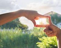 Σύμβολο χεριών μπροστά από το σπίτι στο υπόβαθρο φύσης ηλιοφάνειας στοκ φωτογραφίες
