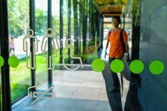 Σύμβολο χώρων ανάπαυσης στον τοίχο γυαλιού με το υπόβαθρο περιπάτων ατόμων Στοκ εικόνες με δικαίωμα ελεύθερης χρήσης