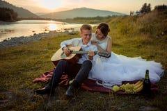 Σύνθεση γαμήλιων πικ-νίκ στην όχθη ποταμού κατά τη διάρκεια του ηλιοβασιλέματος Ο χαμογελώντας νεόνυμφος παίζει την κιθάρα ενώ η  στοκ εικόνες