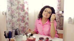 Σύνθεση γυναικών makeup που εφαρμόζει mascara που εξετάζει τον καθρέφτη απόθεμα βίντεο