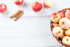 Σύνθεση διάθεσης φθινοπώρου με τα κόκκινα μήλα στο ψάθινο καλάθι και τα κίτρινα φύλλα Στοκ εικόνα με δικαίωμα ελεύθερης χρήσης