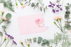 Σύνθεση λουλουδιών Κενό εγγράφου, λουλούδια γαρίφαλων, κλάδοι ευκαλύπτων στο υπόβαθρο κρητιδογραφιών Επίπεδος βάλτε, τοπ άποψη, α στοκ εικόνες