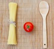 Σύνθεση με τα ακατέργαστα ζυμαρικά, ντομάτα, κουτάλι Στοκ Εικόνα
